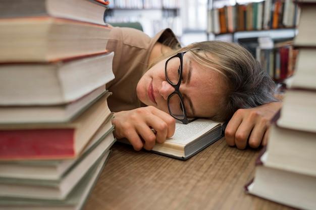 Gros plan femme fatiguée à la bibliothèque