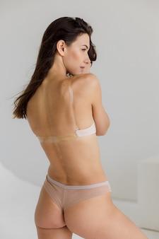 Gros plan femme fit en lingerie isolée sur fond blanc torse d'une femme mince et séduisante avec un ventre plat dans un espace de copie de sous-vêtements blancs pour une photo de haute qualité de texte