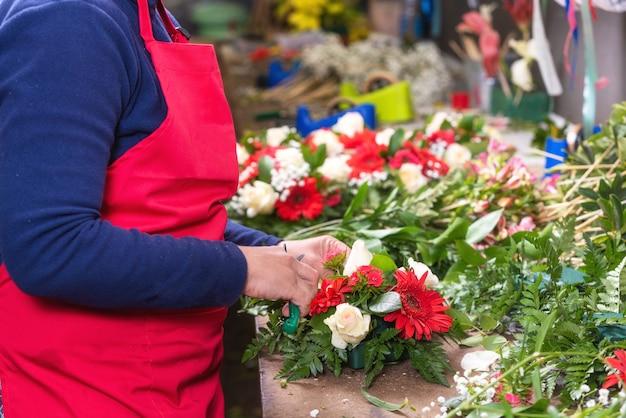 Gros plan de femme fleuriste créant beau bouquet au magasin de fleurs.
