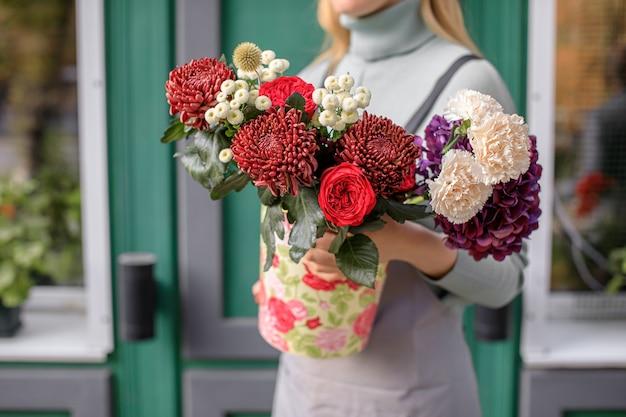 Gros plan de femme fleuriste tenant bouquet au magasin de fleurs.