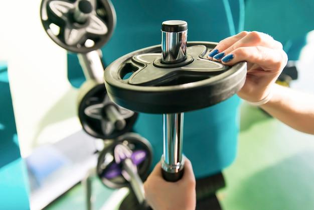 Gros plan, de, femme forte, préparer, séance entraînement, et, ajouter, poids supplémentaire, plaque, pour, barre barre
