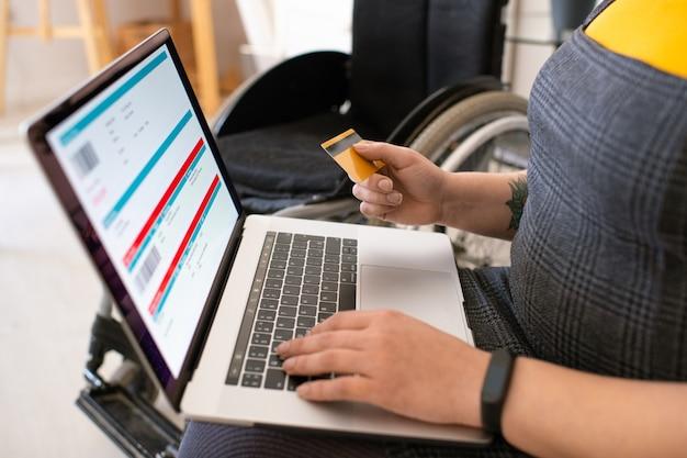 Gros plan d'une femme handicapée méconnaissable, vérification des informations de vol et paiement des billets