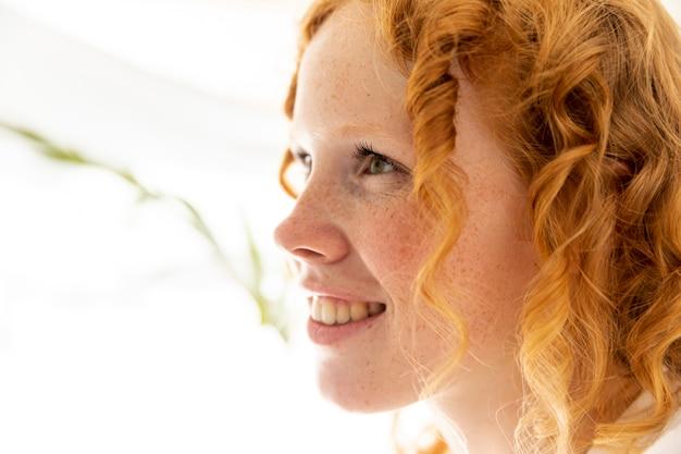 Gros plan femme heureuse avec des cheveux roux