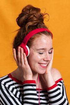 Gros plan femme heureuse, écouter de la musique avec des écouteurs