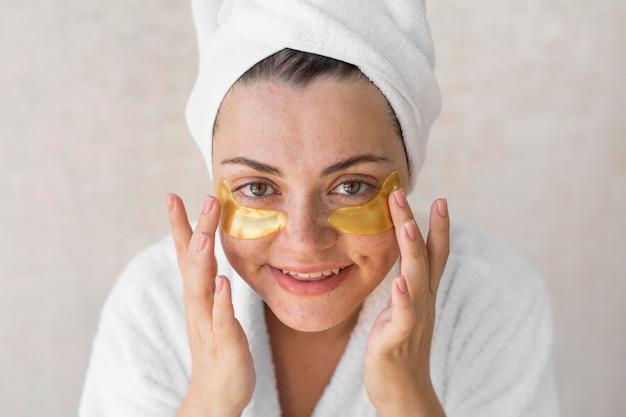 Gros plan femme heureuse avec des patchs oculaires