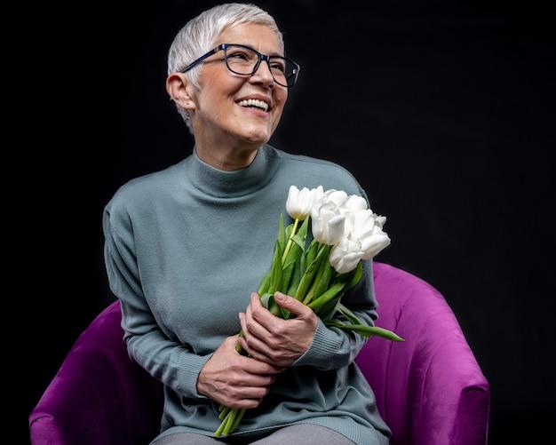 Gros plan d'une femme heureuse tenant un bouquet de fleurs - concept de la journée de la femme