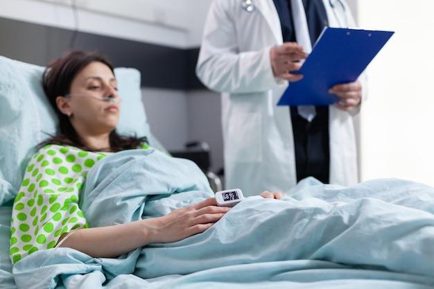Gros plan sur une femme hospitalisée avec un moniteur de fréquence cardiaque au doigt montrant le pouls