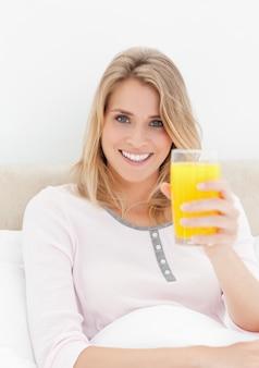 Gros plan, femme avec impatience en souriant tout en brandissant un verre de jus d'orange