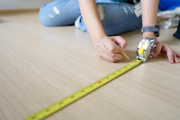 Gros plan femme ingénieur mains avec ruban de menuisier jaune