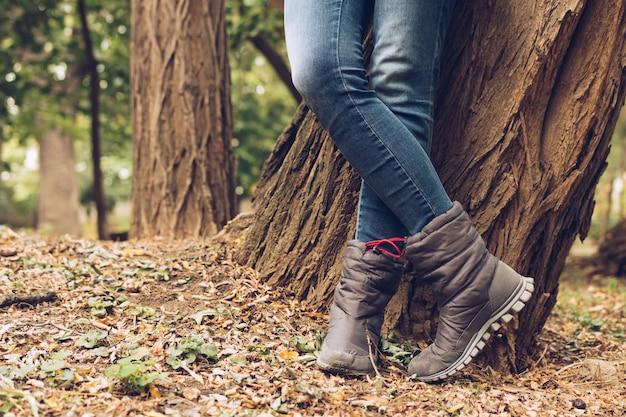 Gros plan, femme, jambes, jeans, bottes, automne, parc