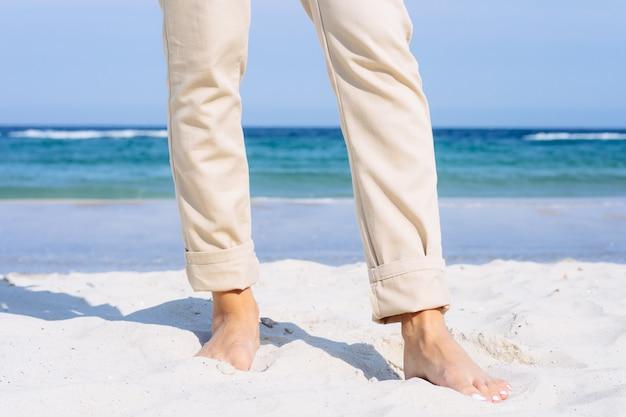 Gros plan, femme, jambes, pantalon beige, pieds nue, plage