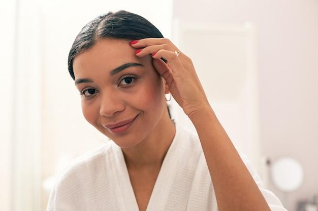 Gros plan de la femme joyeuse et calme debout en peignoir et souriant tout en touchant les cheveux