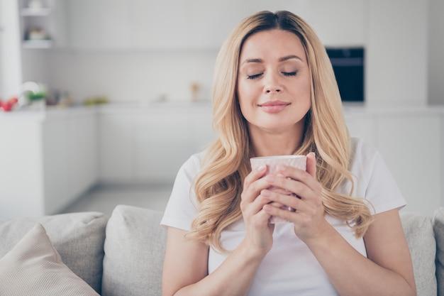 Gros plan femme joyeuse domestique les yeux fermés relaxant s'asseoir confortable canapé tenir mug dream