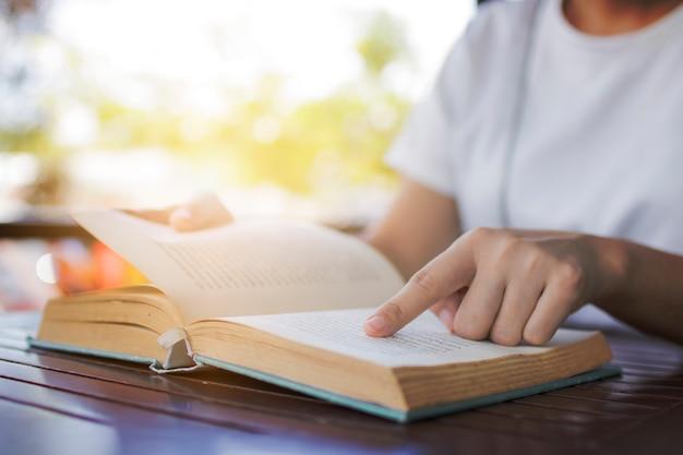 Gros plan, femme, lecture, vieux livre roman, dans, café