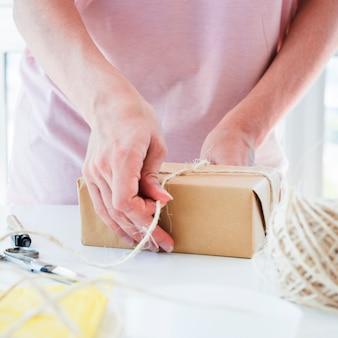 Gros plan, femme, lien, fil, brun, emballé, coffret cadeau, table