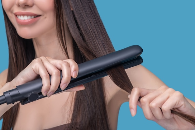 Gros plan d'une femme lissant ses cheveux