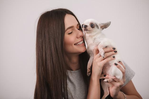 Gros plan d'une femme magnifique en riant, câlins avec son petit chien