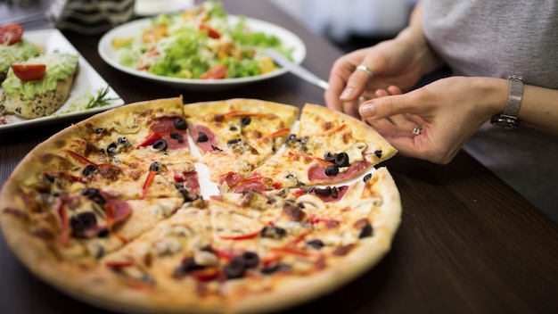 Gros plan, femme, main, prendre, tranche, pizza pepperoni, plaque
