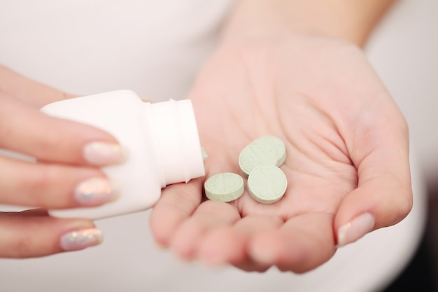 Gros plan femme main tenir pilules