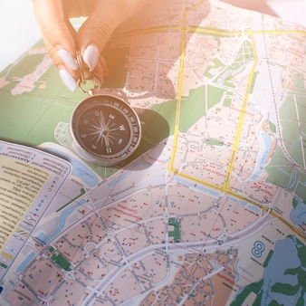 Gros plan, de, femme, main, tenue, navigation, compas navigation, sur, carte