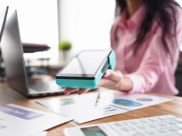 Gros plan, femme, main, tenue, terminal, paiement client payant pour un service ou un produit