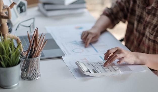 Gros plan femme mains du directeur financier prenant des notes lorsqu'il travaille sur un rapport