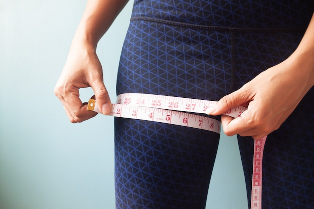 Gros plan femme mains mesurant ses jambes