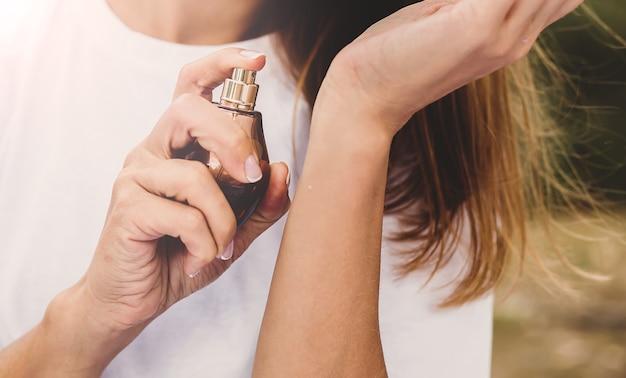 Gros plan, de, femme, mains, pulvérisation parfum