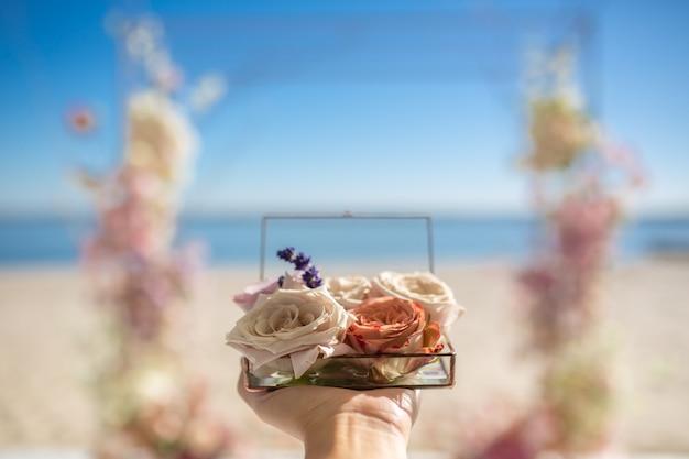Gros plan femme mains tenir boîte de verre pour les alliances décorées avec des fleurs roses fraîches et bouquet de lavande
