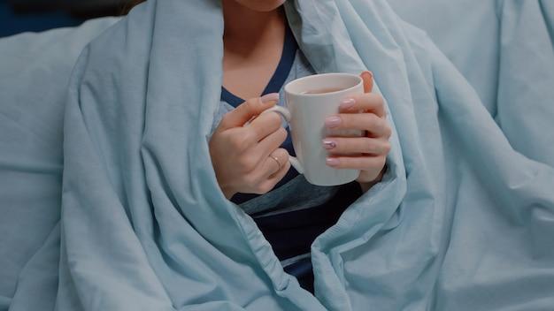 Gros plan d'une femme malade avec une couverture tenant une tasse de thé