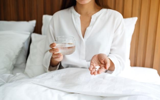 Gros plan d'une femme malade tenant des pilules blanches et un verre d'eau en position couchée sur un lit