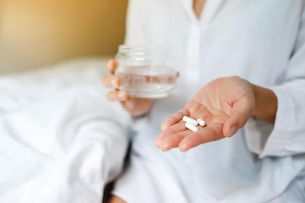 Gros plan d'une femme malade tenant des pilules blanches et un verre d'eau tout en étant assis sur un lit