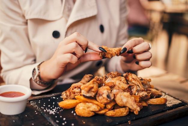Gros plan d'une femme mangeant des ailes de poulet.