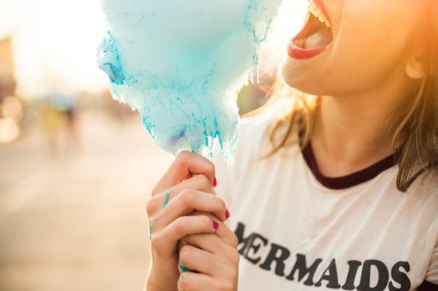 Gros plan d'une femme mangeant de la barbe à papa bleue