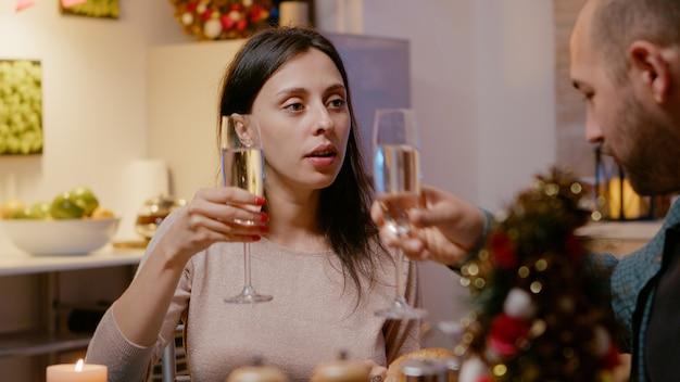 Gros plan d'une femme mangeant de la nourriture et tinter le verre de champagne