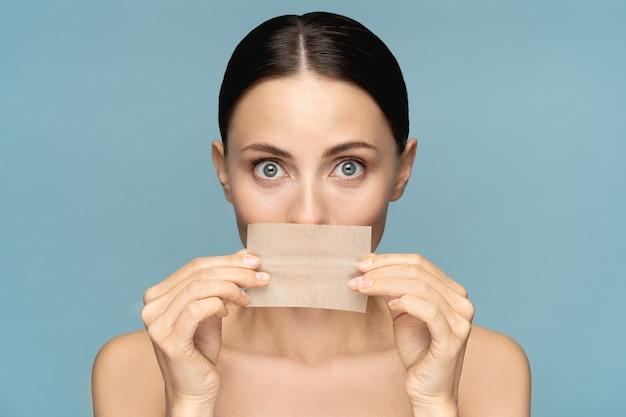Gros plan d'une femme avec un maquillage naturel pour le visage, tenant du papier buvard à l'huile pour le visage
