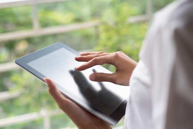 Gros plan d'une femme méconnaissable à l'aide de tablette numérique.
