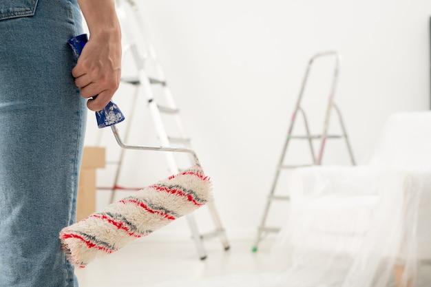 Gros plan d'une femme méconnaissable en jeans tenant le rouleau de peinture dans la chambre avec escabeaux