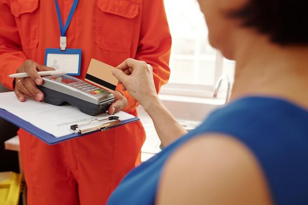 Gros plan sur une femme méconnaissable payant un service de réparation avec une carte de crédit via un terminal détenu par un militaire avec un presse-papiers