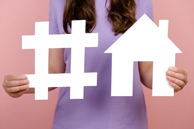 Gros plan d'une femme méconnaissable tenant un signe de hashtag blanc et un modèle de maison, une étiquette pour les entreprises, le marketing, la publicité, isolés sur un mur rose. veille réseaux sociaux, mesure média, crédit immobilier