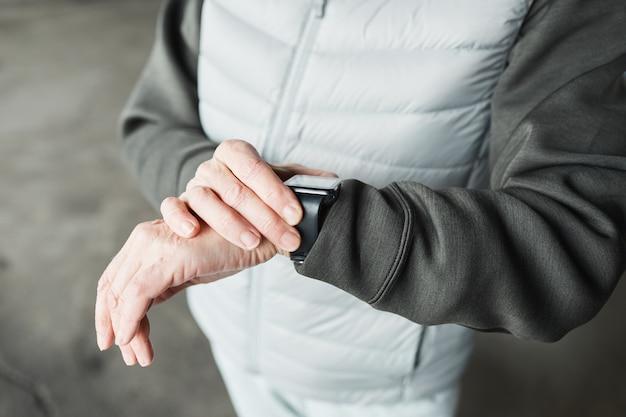 Gros plan sur une femme méconnaissable en vêtements chauds vérifiant le pouls sur une montre intelligente après un entraînement en plein air