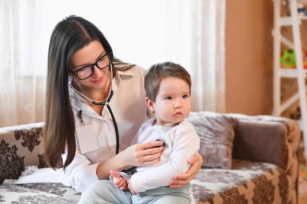 Gros plan d'une femme médecin avec stéthoscope à l'écoute du rythme cardiaque ou de la respiration du patient à la maison