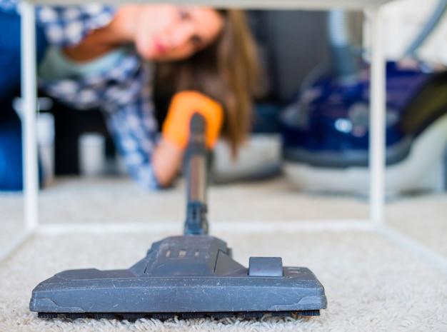 Gros plan d'une femme de ménage nettoyant un tapis avec un aspirateur