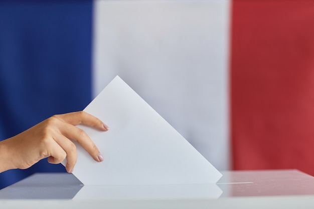 Gros plan de femme mettant l'enveloppe dans la boîte pendant le vote