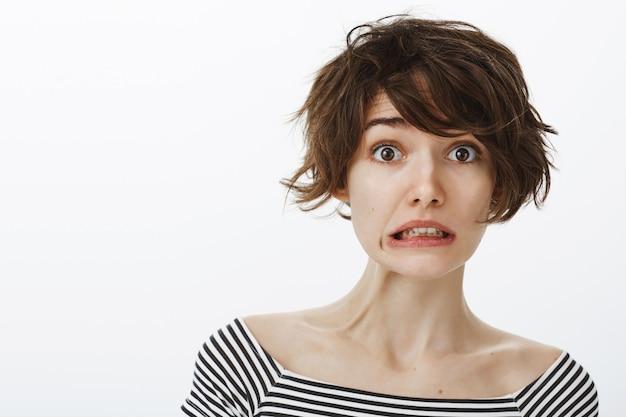 Gros plan d'une femme mignonne maladroite et embarrassée, serrant les dents et l'air inquiet