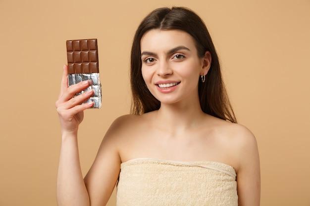 Gros plan sur une femme à moitié nue avec une peau parfaite, un maquillage nu tient une barre de chocolat isolée sur un mur pastel beige