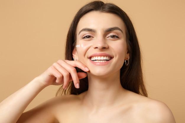 Gros plan femme à moitié nue avec une peau parfaite maquillage nude appliquant une crème pour le visage isolée sur un mur pastel beige
