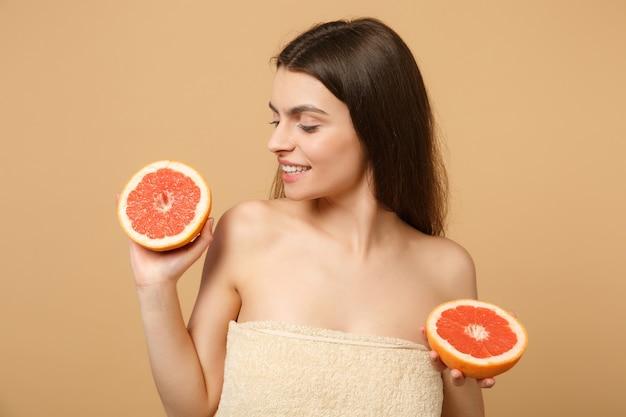 Gros plan femme à moitié nue avec une peau parfaite maquillage nude tient pamplemousse isolé sur mur pastel beige