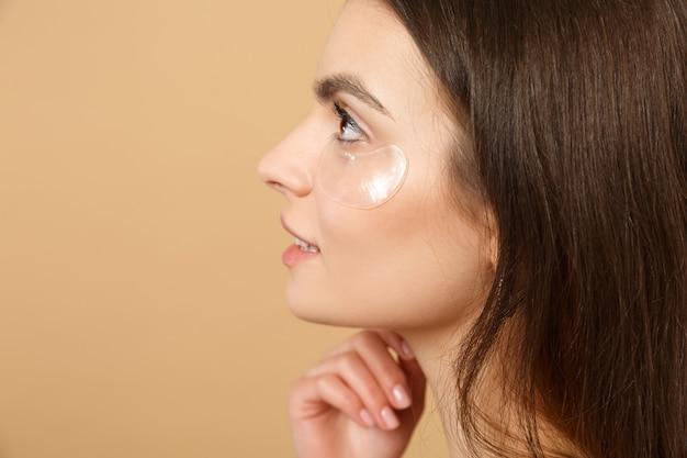Gros plan sur une femme à moitié nue avec une peau parfaite, des patchs de maquillage nus sous les yeux isolés sur un mur pastel beige