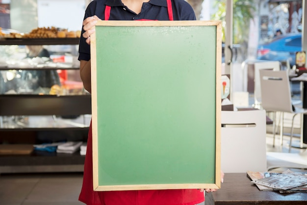 Gros plan de femme montrant un tableau de menu vide dans un café